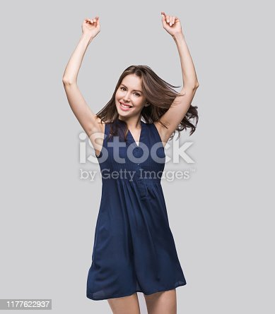 638678178 istock photo Laughing young woman with raised arms having fun 1177622937