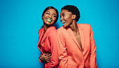 Laughing young women in stylish clothing standing back to back. Female friends standing together in studio over blue background.