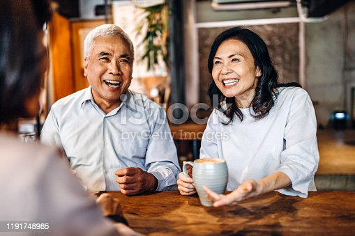 Group of three Asian senior friends sitting and talking in cafe, laughing and having fun