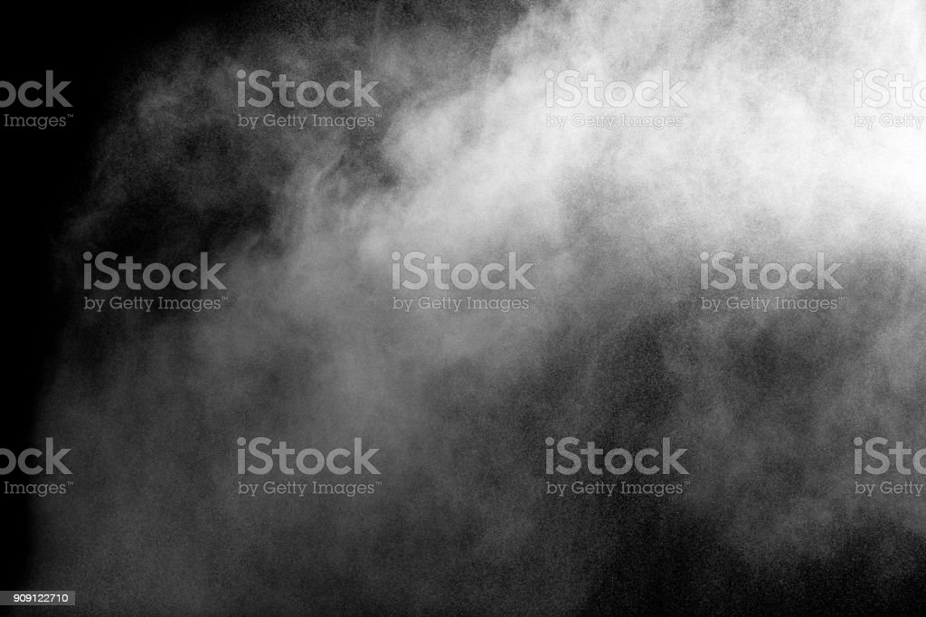 Launched white particle splash on black background. Bizarre forms of of white powder explosion cloud against dark background. stock photo