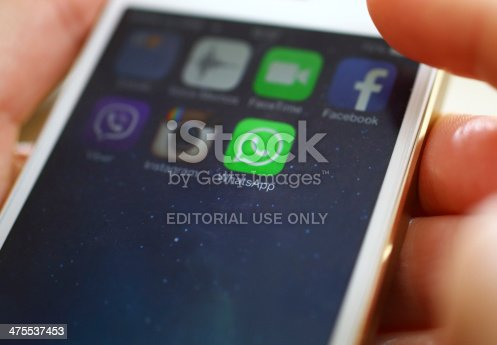Wien,Austria-February 25,2014: Closeup of female hand holding an iPhone 5s while launching WhatsApp,a popular messaging application .