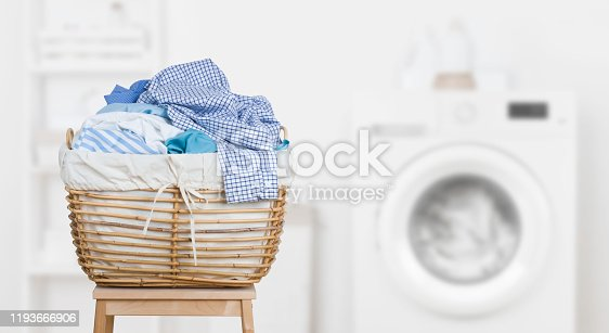 Laundry basket on blurred background of modern washing machine