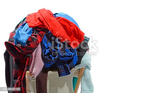 Horizontal shot of an overstuffed laundry hamper isolated on white with copy space of the right side of image.