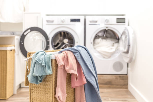 Laundry basket with dirty clothes with washing and drying machines on the background stock photo