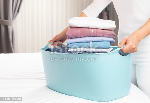 Women holding laundry basket and ironed shirts at home.
