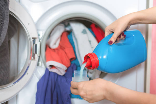 Laundry, cleaning agent advertisement. Woman is holding in hands a liquid laundry detergent on a washing machine background. laundry detergent stock pictures, royalty-free photos & images