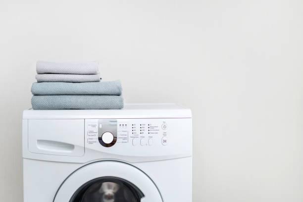 wäschekonzept. geschnittene fotografie von weißer und moderner waschmaschine mit frischem handtuch auf dem dach stehend isoliert im hellen wohnraum - waschmaschine fotos stock-fotos und bilder