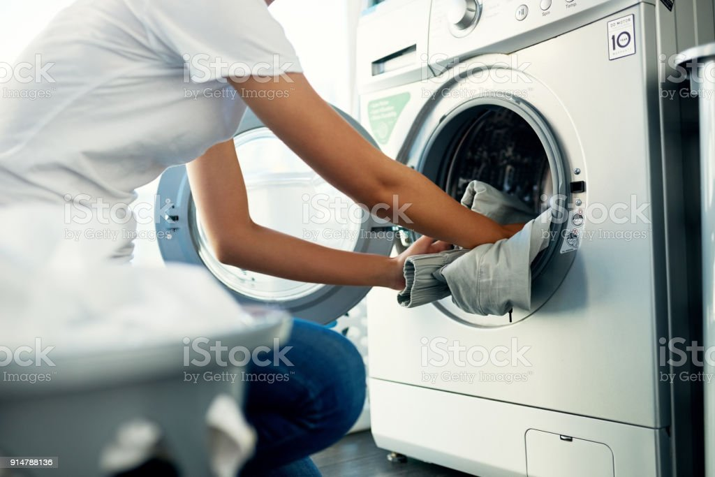 Laundry day comes around once every week Shot of a young woman doing her laundry at home Adult Stock Photo