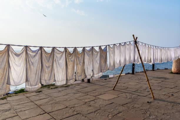 tvätt torkning på rep på ghat i solig dag. varanasi. indien - working from home bildbanksfoton och bilder