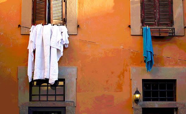wäsche aufhängen gegen orange römischer wall, italien - orangenscheiben trocknen stock-fotos und bilder