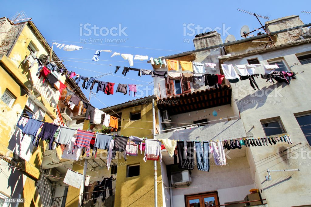 Laundry hanging on a clothes line on an old city building. Hanging Laundry and walls. Washing hanging on clothes lines between buildings. Drying clothes hanging outside the window of an old facade. stock photo