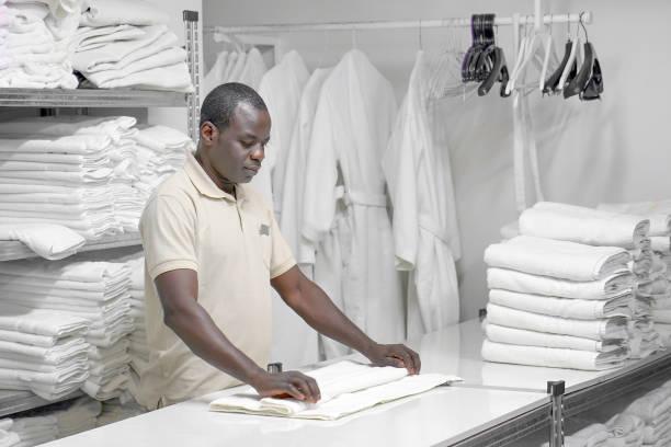 Wäschereihotel. Ein Mann legt ein weißes Handtuch aus. – Foto