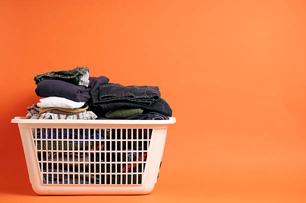 Laundry in a Basket Color photo of folded men's clothing in a laundry basket on an orange background. Room for text above and on right. laundry basket stock pictures, royalty-free photos & images