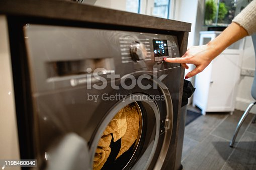 A close-up shot of an unrecognisable caucasian woman pressing a button on her washing machine.