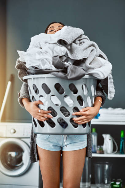 Laundry might be taller than me but I will conquer it Shot of an unrecognizable woman doing her laundry at home laundry basket stock pictures, royalty-free photos & images
