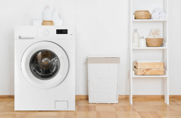 Laundry room interior with washing machine and shelf near wall stock photo