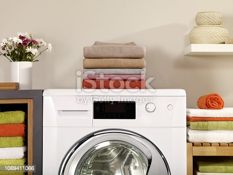 folded wool shirts on a washer in a laundry room
