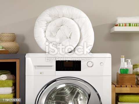 Folded quilt on a washer in a laundry room