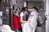 Female worker in laundry service,get washed sheets out of washing machine