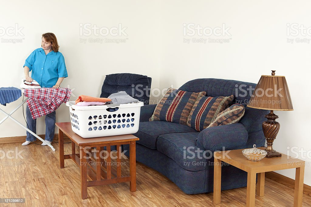 Laundry: Woman Ironing and Folding Clothes stock photo