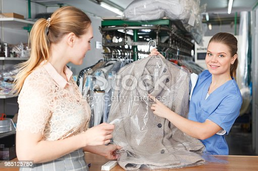 istock Laundry worker giving clean clothes to client 985125780