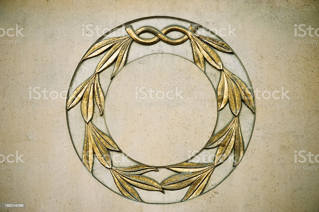 Laurel Wreath in Gold Relief on Stone Wall royalty-free stock photo