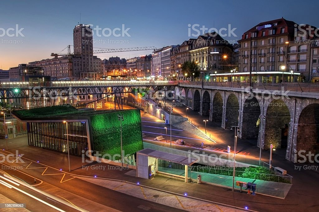 Lausanne Flon at twilight, Switzerland HDR image at sunset of the new development area of Flon in downtown Lausanne, Switzerland. In recent years the former industrial area was fully transformed into a modern recreation area as well as an transportation node. The green covered building is the new entrance to the subway station of M2 metro, linking the south and north parts of the city by one of the steepest metro lines in the world. Arch - Architectural Feature Stock Photo