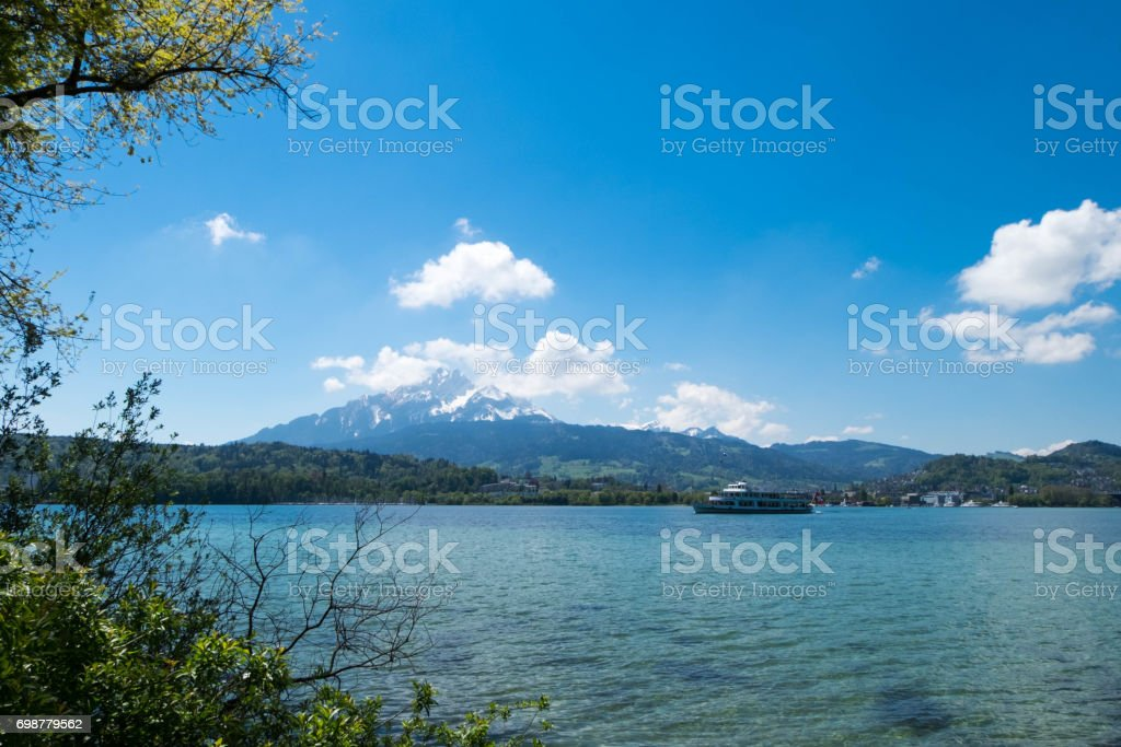 Lausanne lake landscape under blue sky. There is a traveled ship and mountain as background. stock photo