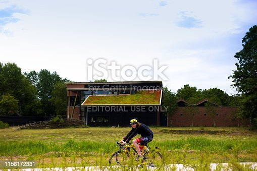Lauwersoog, Groningen, Netherlands: A couple on bikes rides past an eco-friendly house with a living roof. Lauwersoog is located on the north coast of Holland.