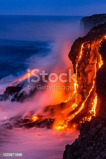Lava falls over the cliff into the ocean at Kilauea