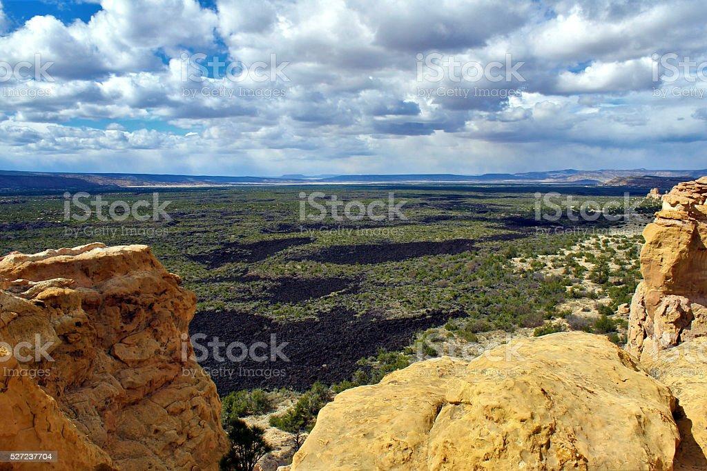 Lava Fields Beyond Sandstone Bluffs of El Malpais stock photo