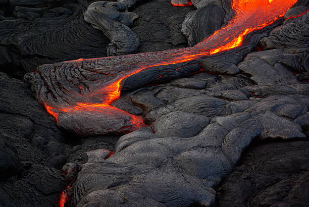 Lava flow on the Big Island of Hawaii Tongue of glowing red lava flowing from the 2013 Puu oo lava flow.  Picture shows flowing lava crossing over recently cooled lava (grey) on a background of cooled lava (dark). lava stock pictures, royalty-free photos & images