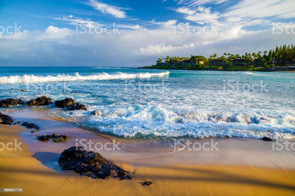lava rock, golden sand, white foam, napili bay, maui stock photo