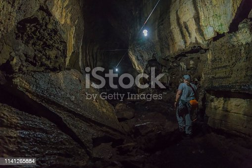Mature woman walking in lava tunnel. Santa Cruz island, Galapagos islands.