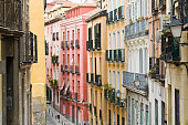 Colorful apartment blocks and iron balconies line a narrow side street in the Lavapies district of Madrid, Spain. Adobe RGB 1998 color profile.