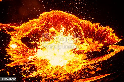 Lave explosion during eruption of volcano Erta Ale - one of the most active vulancoes in the world - into the active, red glowing lava lake. Erta Ale is a continuously active basaltic shield volcano in the Afar Region of northeastern Ethiopia, only some kilometers from the border to Eritrea.