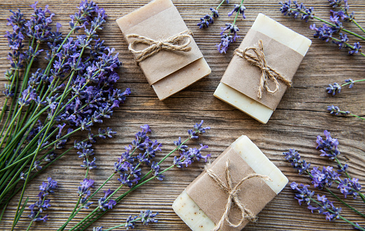 Bars of handmade soap with lavender flowers over  wood grunge background.