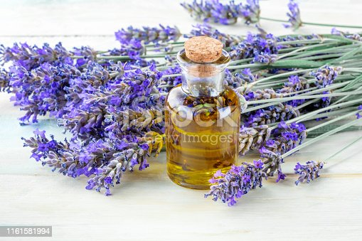 Lavender essential oil with fresh lavender flowers on a rustic wooden background with a place for text