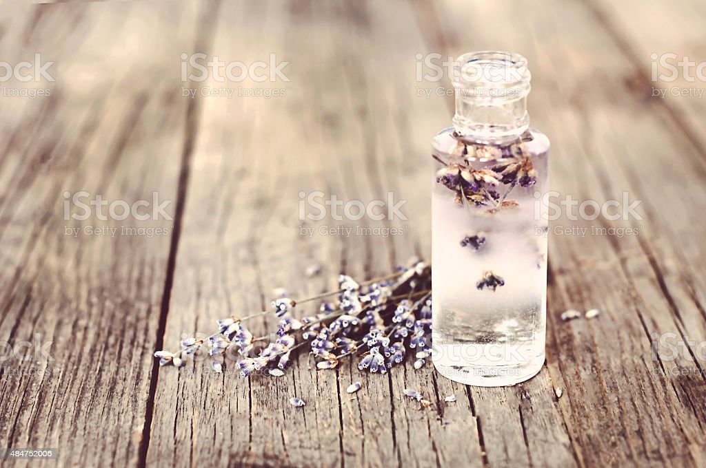 Lavender flowers and glass bottles on a wooden surface stock photo