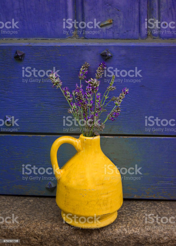 Lavender In A Yellow Vase On A Background Of Purple Shabby Door