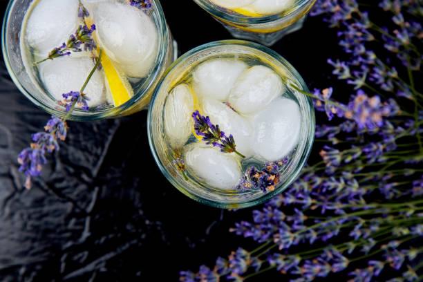 Lavendellemonade mit Zitrone und Eis auf schwarzem Hintergrund. – Foto