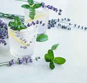 Lavender lemonade with lemon , mint, ice cubs, lavender flowers on blue background. Detox water, summer drink.  Top view. Copy space
