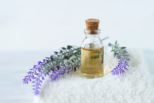 Front view of lavender in oil and  lavender flowers on a white towel on marble background.