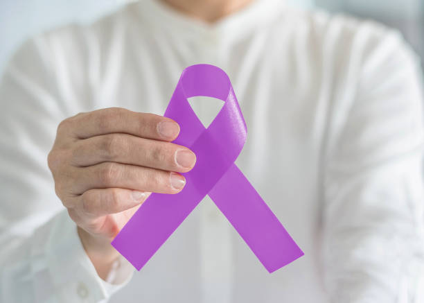 lavender purple cancer awareness ribbon on person's hand, symbolic bow color  to support patient with all kinds tumor, national cancer survivors month and epilepsy illness - ovarian cancer ribbon stock pictures, royalty-free photos & images