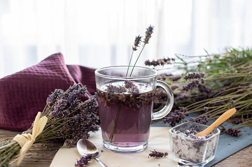 Lavender tea rustic on wood in a glass teacup. Lavender (Lavandula angustifolia), has a calming and antispasmodic effect.