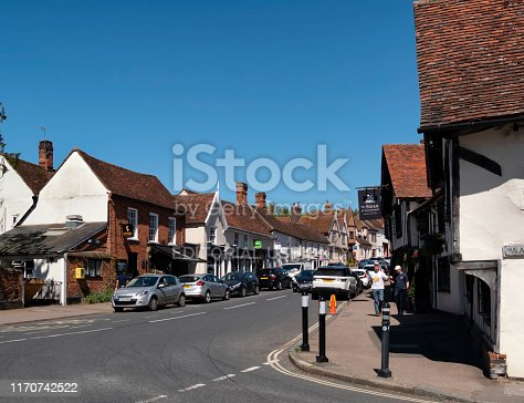 A few people walking near the famous Swan Hotel in the High Street in Lavenham, Suffolk, Eastern England, on a sunny spring day. Lavenham is an historic market town, once a wealthy medieval 'wool town' which is popular with tourists who are enchanted by its many beautiful ancient buildings.