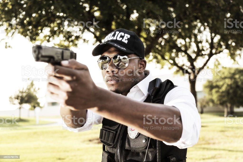 Law:  African descent policeman aims his gun at criminal. stock photo