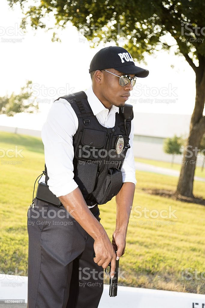 Law: African descent policeman gets gun ready to shoot. stock photo