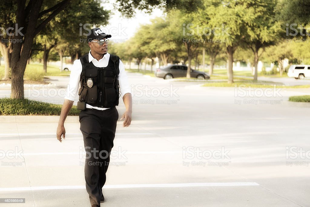 Law:  African descent policeman investigates crime.  City streets. stock photo
