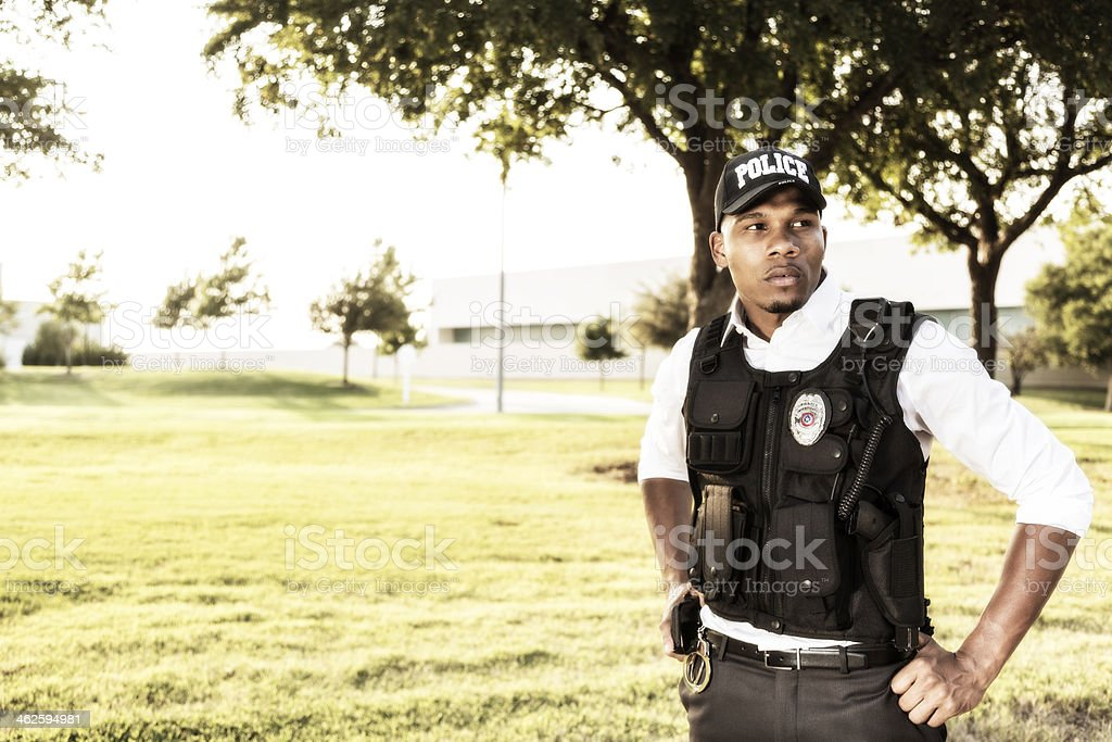 Law:  African descent policeman on the job.  Urban area. stock photo